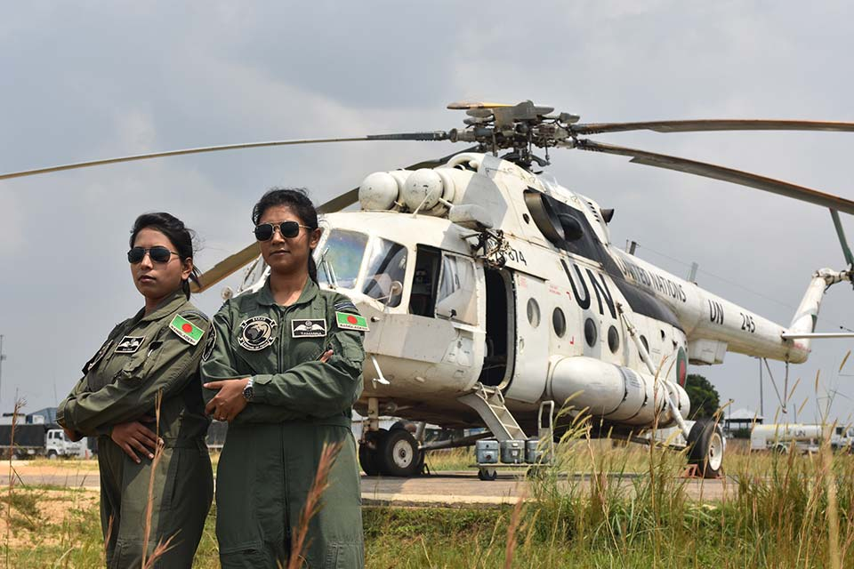 Deployed women pilots from Bangladesh pose in front of helicopter