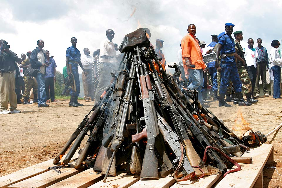 Civilians pass by large pile of collected armaments
